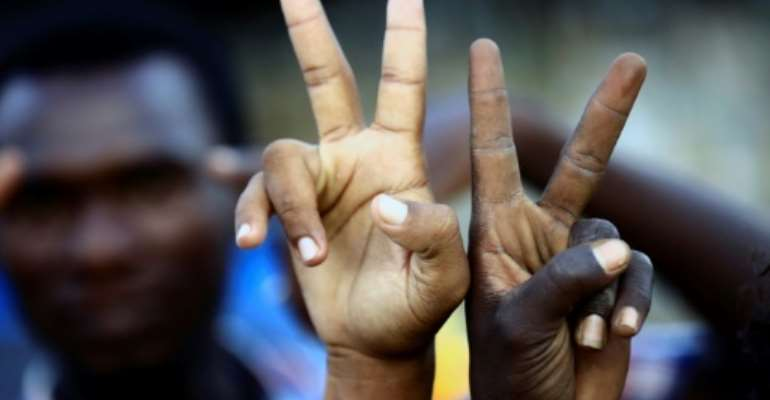 Sudanese demonstrators flash V-for-victory signs as they gather outside the military headquarters in Khartoum in the capital Khartoum on May 20, 2019.  By ASHRAF SHAZLY (AFP)