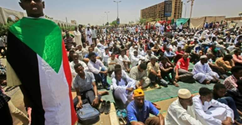 Sudanese demonstrators hold Friday prayers at the protest camp outside army headquarters in Khartoum.  By ASHRAF SHAZLY (AFP)