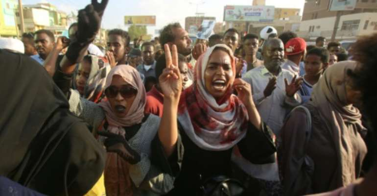 Sudanese demonstrators march during a protest in Khartoum urging the country's new authorities to dissolve the former ruling party of ousted Islamist leader Omar al-Bashir.  By ASHRAF SHAZLY (AFP)