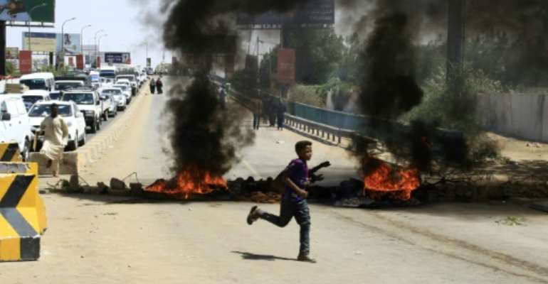 Sudanese demonstrators set fire to tyres to block a Khartoum road as the five-month protests show no signs of abating.  By EBRAHIM HAMID (AFP)
