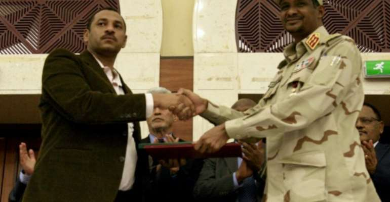Sudanese deputy chief of the ruling miliary council Mohamed Hamdan Dagalo and protest movement Alliance for Freedom and Changes leader Ahmad al-Rabiah shake hands after inking a power-sharing agreement.  By Ebrahim HAMID (AFP)