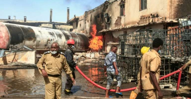 Sudanese firefighters tackle the deadly blaze in a north Khartoum ceramics factory.  By Ebrahim HAMID (AFP)