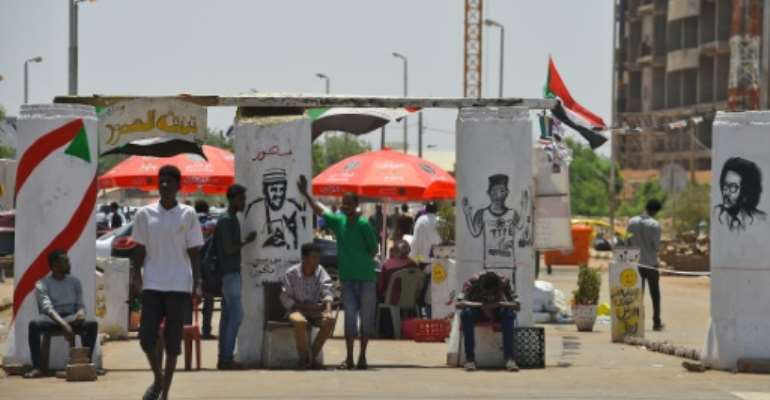 Sudanese graffiti artists commemorate five protesters shot dead at a longrunning sit-in outside army headquarters overnight in what protest leaders charged was a bid to derail talks with the country's military rulers.  By Mohamed el-Shahed (AFP)