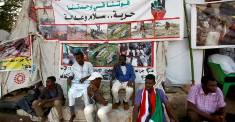 Sudanese men displaced from Darfur sit next to a tent outside the military headquarters in the capital Khartoum at the ongoing sit-in.  By ASHRAF SHAZLY (AFP)