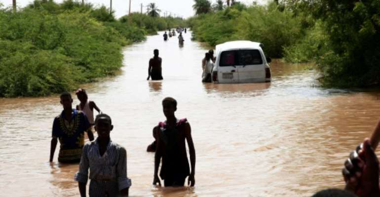 Sudanese people walk a flooded road in Wad Ramli village on the eastern banks of the Nile river.  By Ebrahim HAMID (AFP)