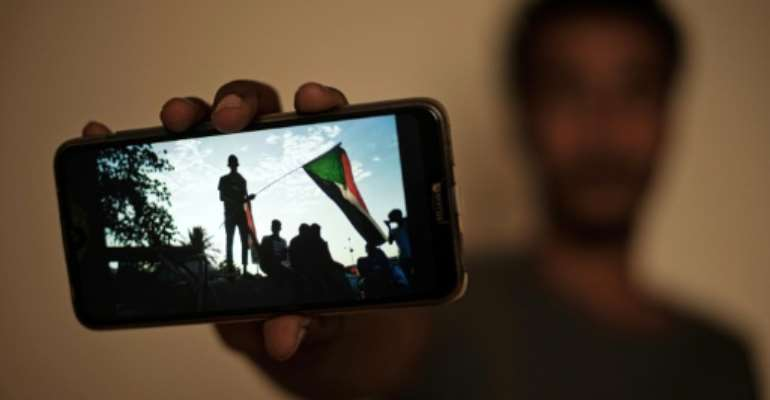 Sudanese protester Akram, who prefers to keep his identity hidden, shows a picture from a sit-in brutally cleared by men wearing military fatigues on June 3.  By - (AFP)