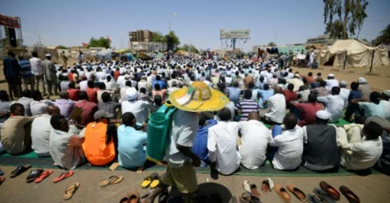 Sudanese protesters, attending Friday prayers near the military headquarters, have kept a sit-in at the site for weeks.  By MOHAMED EL-SHAHED (AFP)