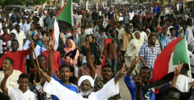Sudanese protesters chant slogans and flash the victory sign as they march with national flags during a mass demonstration against the country's ruling generals in Khartoum.  By Ebrahim Hamid (AFP)