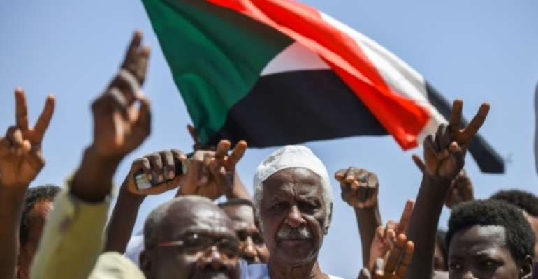 Sudanese protesters chant slogans, flash V-for-victory signs and wave the national flag at the sit-in outside the army headquarters in the capital Khartoum on May 14, 2019.  By Mohamed el-Shahed (AFP)