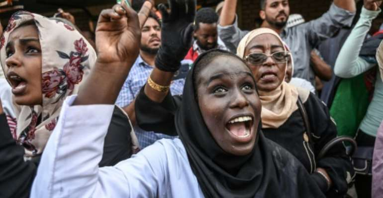 Sudanese protesters cheer fellow demonstrators arriving in Khartoum by train.  By OZAN KOSE (AFP)