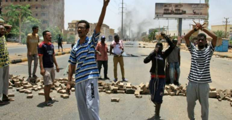 Sudanese protesters gesture and chant slogans outside Khartoum's army headquarters on June 3, 2019 after security forces broke up a weeks-long sit-in, prompting the US to call for an