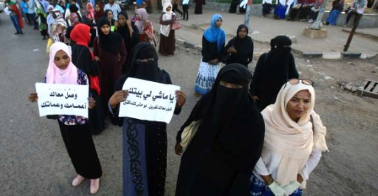 Sudanese protesters hold signs that read: