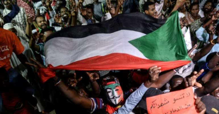 Sudanese protesters kept up their sit-in outside Khartoum's army headquarters on Sunday night to press for civilian government.  By Mohamed el-Shahed (AFP)