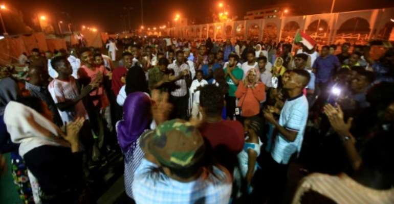 Sudanese protesters near the military headquarters in the capital Khartoum on Friday, at an ongoing sit-in aimed at pressuring the army council to hand over power to civilians.  By ASHRAF SHAZLY (AFP)
