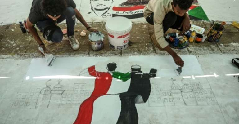 Sudanese protesters paint a mural during a sit-in outside the army headquarters in the capital Khartoum on April 28, 2019.  By OZAN KOSE (AFP)