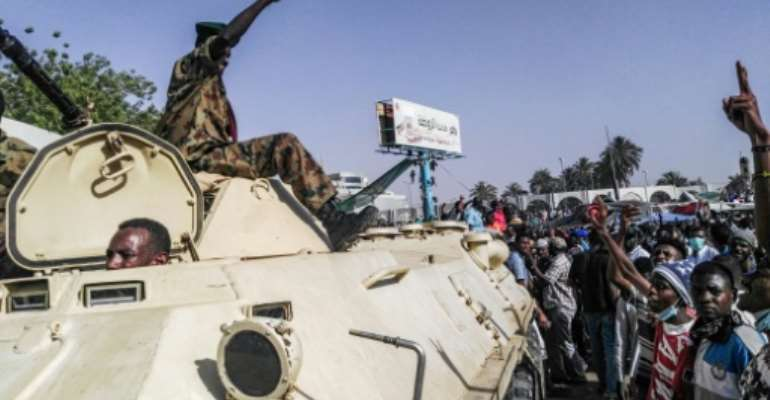Sudanese protesters salute a military armoured vehicle at a demonstration in front of the army headquarters in Khartoum, as some ranks appear to be tiling towards the rallies.  By - (AFP)