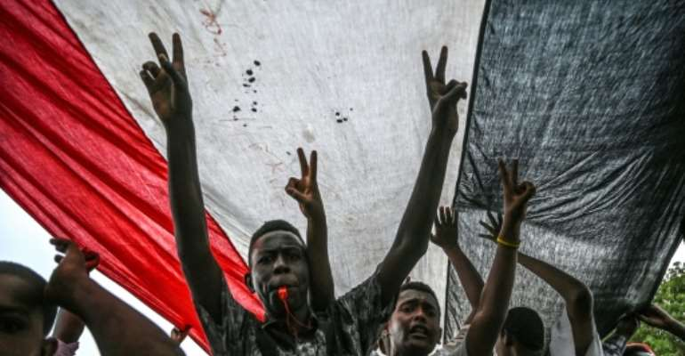 Sudanese protesters shout slogans and flash victory signs during a rally outside the army complex in Sudan's capital Khartoum.  By OZAN KOSE (AFP)