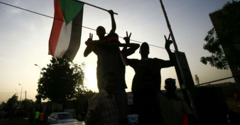 Sudanese protesters wave the national flag outside the military headquarters in the capital Khartoum on May 19, 2019 as talks were to resume between the military rulers and leaders of the demonstrators on a new governing body.  By ASHRAF SHAZLY (AFP)