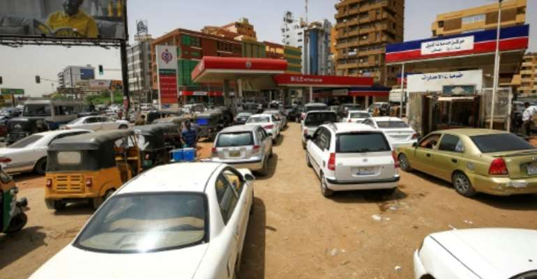 Sudanese queue up at petrol stations to fill up after the government decided to scrap subsidies on petrol and diesel, more that doubling prices.  By ASHRAF SHAZLY (AFP)