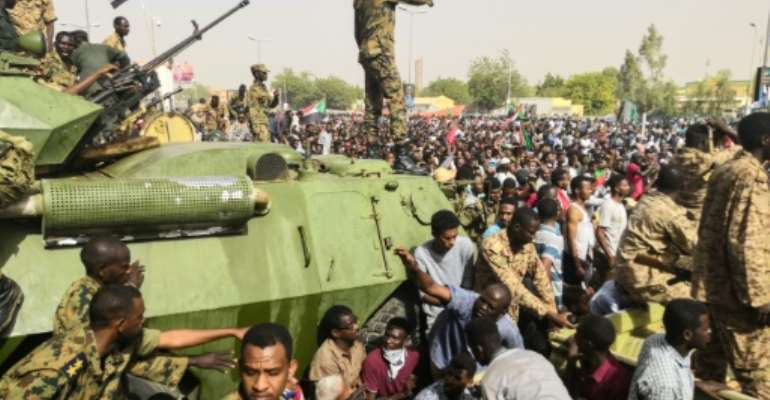 Sudanese soldiers stand guard on armoured military vehicles as demonstrators continue their  protest against the regime near army headquarters in the Sudanese capital Khartoum on April 11, 2019.  By - (AFP)