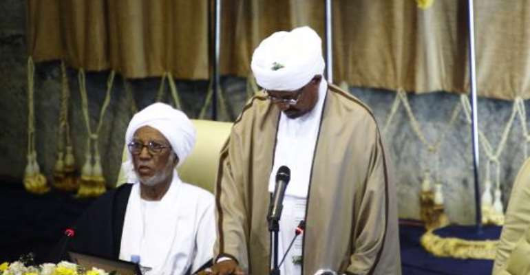 Sudanese President Omar al-Bashir (R) puts his hand on a copy of the Koran, during his swearing in ceremony for another term of five years at the parliament in Khartoum on June 2, 2015.  By Ashraf Shazly (AFP/File)