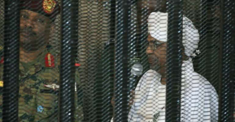 Sudan's deposed military ruler Omar al-Bashir stands in a defendant's cage at the opening of his corruption trial in Khartoum in August.  By Ebrahim HAMID (AFP)