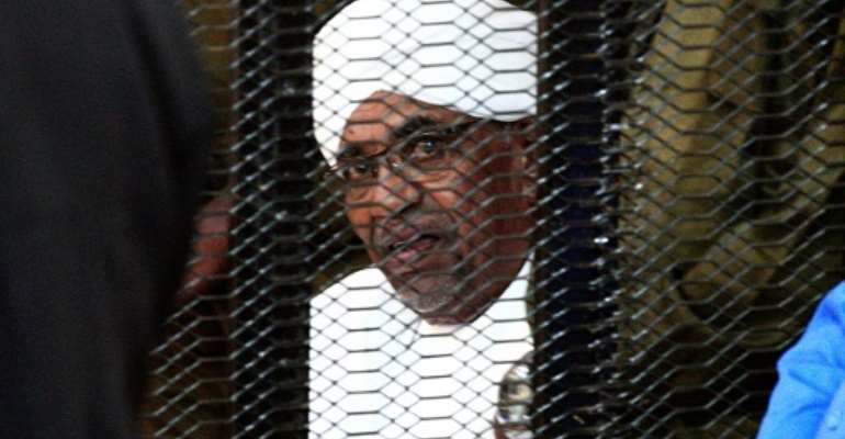Sudan's deposed president Omar al-Bashir looks on from a defendant's cage during the opening of his corruption trial in Khartoum on August 19, 2019.  By Ebrahim HAMID (AFP/File)