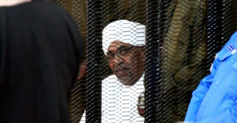 Sudan's deposed ruler Omar al-Bashir sits in a defendant's cage during his corruption trial in Khartoum.  By Ebrahim HAMID (AFP)