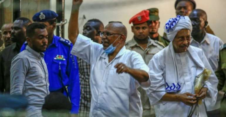 Sudan's ousted president Omar al-Bashir (C) gestures on arrival for his trial in the capital Khartoum along with 27 co-accused over the 1989 military coup that brought him to power.  By ASHRAF SHAZLY (AFP)