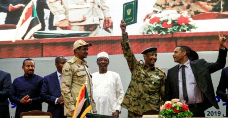 Sudan's protest leader Ahmad Rabie (R), flashes the victory gesture alongside General Abdel Fattah al-Burhan (2nd-R), the chief of the military council, after signing the