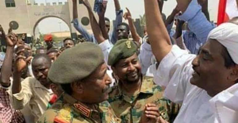 Sudan's second new military ruler in as many days, Lieutenant General Abdel Fattah al-Burhan, is seen talking with protesters outside army headquarters in a photograph released by state news agency SUNA.  By - (SUDAN NEWS AGENCY/AFP)