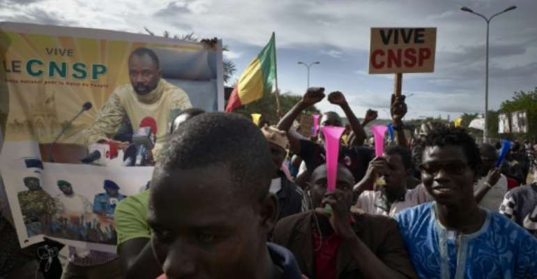 Supporters of the junta, which calls itself the CNSP (National Committee for the Salvation of the People), walk past a banner depicting its leader Assimi Goita in a rally in Bamako on Wednesday.  By MICHELE CATTANI (AFP)