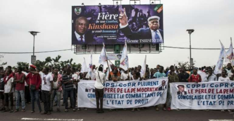 Supporters of the late Congolese opposition leader Etienne Tshisekedi outside the airport ahead of the arrival of his body.  By John WESSELS (AFP)