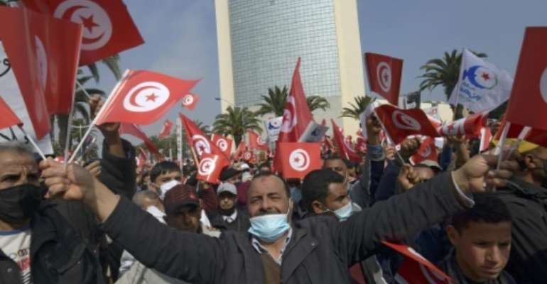 Supporters of Tunisia's Islamist-inspired Ennahdha party wave national flags during a demonstration in Tunis in support of the government following a cabinet reshuffle rejected by the country's president.  By FETHI BELAID (AFP)
