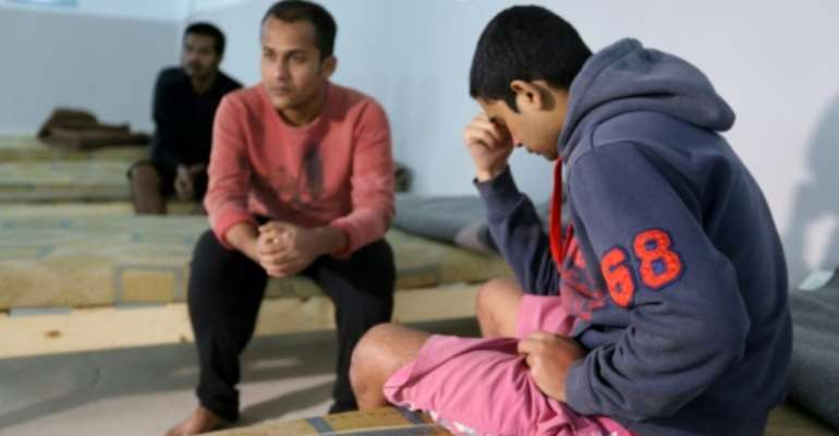 Survivors of a migrants shipwreck that killed around 60 people sit in a Tunisian shelter after being rescued at sea.  By FATHI NASRI (AFP)