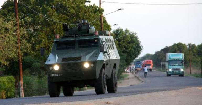 A police armoured vehicle escorts commercial trucks traveling from Muxungue in Sofala province on October 29, 2013.  By Ferhat Momade (AFP/File)