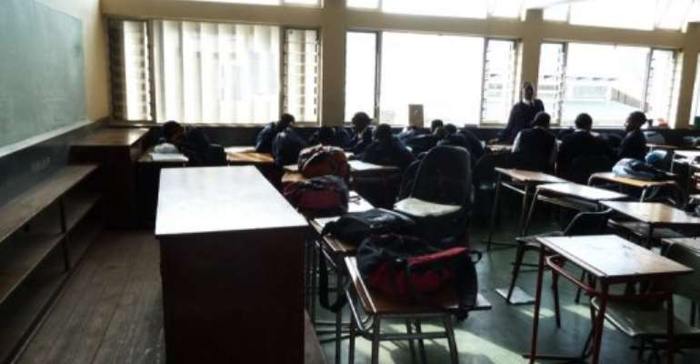 A group of pupils laugh, play or sleep in an empty geography class at St. Mark's High School in Mbabane on July 24.  By Johannes Myburgh (AFP/File)