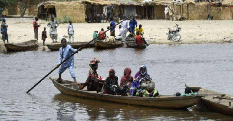 People cross a branch of Lake Chad on April 6, 2015, in N'Bougoua, which was attacked by Boko Haram.  By Philippe Desmazes (AFP/File)