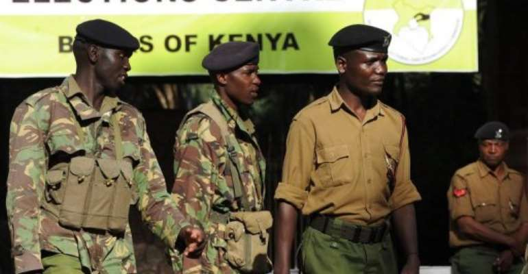 Kenyan police stand guard at the entrance of a polling station where March 7,2013 in Nairobi.  By Simon Maina (AFP)