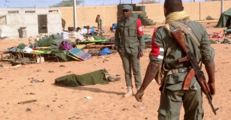 The body of a dead soldier is covered with a blanket after a suicide bomb attack ripped through a camp of former rebels and pro-government militia in northern Mali on January 18, 2017.  By  (AFP)