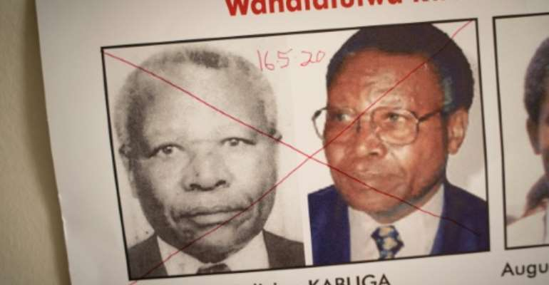 The date of arrest and a red cross are written on the face of Felicien Kabuga, one of the last key suspects in the 1994 Rwandan genocide, on a wanted poster at the Genocide Fugitive Tracking Unit office in Kigali.  By Simon Wohlfahrt (AFP)