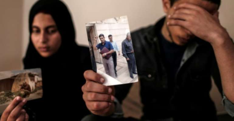 The daughter and son (pictured April 2019) of Zaki Mubarak, whose body was transferred to Cairo after Ankara said he had committed suicide in prison, hold his picture during an interview in their family home.  By MAHMUD HAMS (AFP/File)