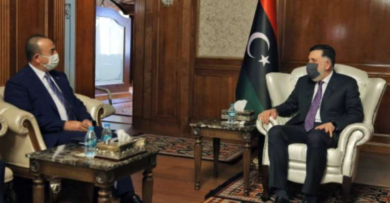 The head of Libya's UN-recognised Government of National Accord Fayez al-Sarraj (R) holds talks in Tripoli with Turkish Foreign Minister Mevlut Cavusoglu whose country backs the GNA in its fight against eastern-based Libya strongman Khalifa Haftar.  By - (AFP)
