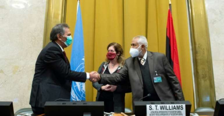 The heads of the rival Libyan delegations shake hands in front of the UN envoy after agreeing to a