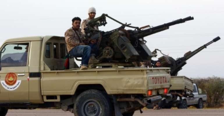 Members of a brigade loyal to Libya Dawn, an alliance of Islamist-backed militias, sit on a pick up truck mounted with a machine gun on March 15, 2015 in Libya's coastal city of Sirte.  By Mahmud Turkia (AFP/File)