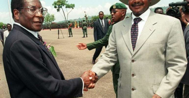 The late Zimbabwean leader Robert Mugabe (who was president for 37 years) with Uganda's President Yoweri Museveni (34 years and counting) in 1998.  By ALESSANDRO ABBONIZIO (AFP/File)