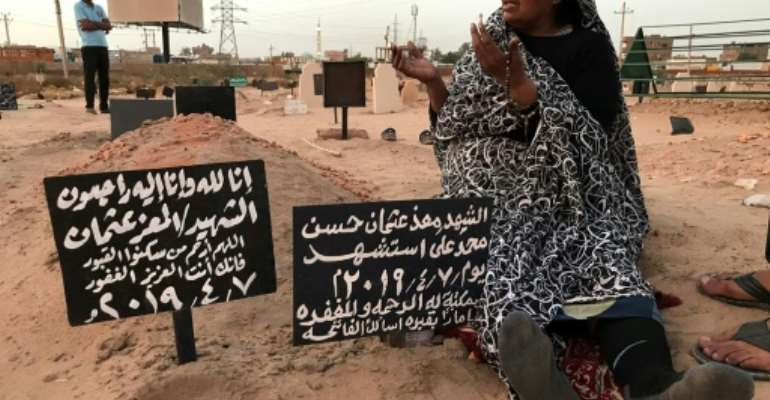 The mother of Al-Moez visits the tomb of her son, killed when a bullet pierced the window of his workplace and struck him in the heart during unrest in the Sudanese capital Khartoum.  By Claire DOYEN (AFP)