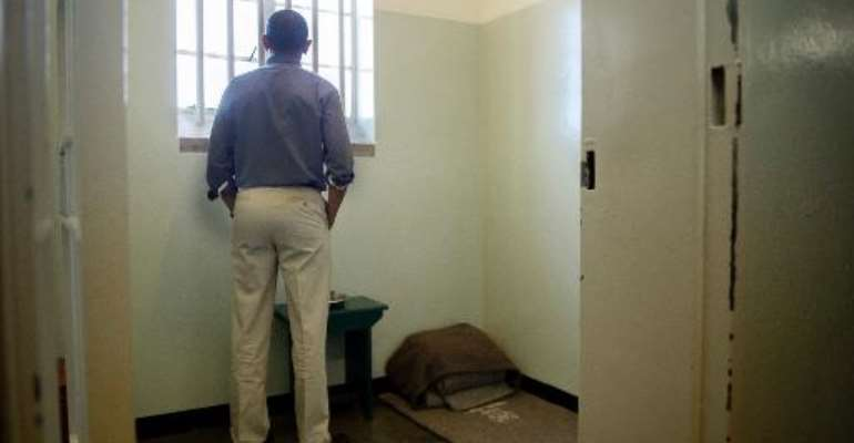US President Barack Obama looks out the window from the cell where Nelson Mandela was once jailed on Robben Island, on June 30, 2013.  By Jim Watson (AFP/File)