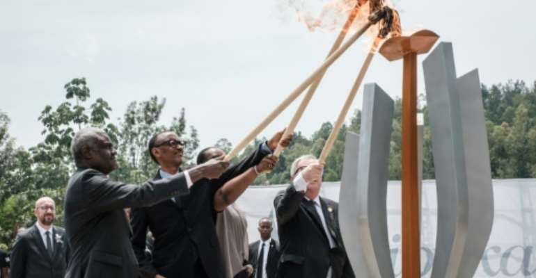 The Rwandan president, centre, lit the remembrance flame along with African Union chief Moussa Faki and Rwandan First Lady Jeannette Kagame.  By Yasuyoshi CHIBA (AFP)