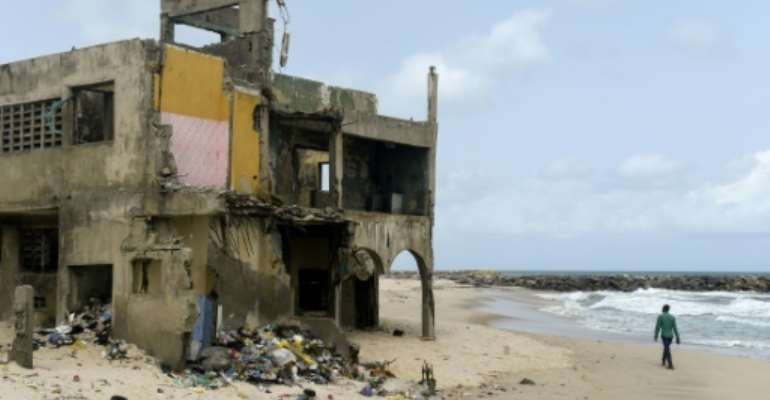 The shore-hugging Alpha Beach road has disappeared under the waves and apartment blocks built with prized ocean views just 10 years ago are now occupied only by squatters.  By PIUS UTOMI EKPEI (AFP)